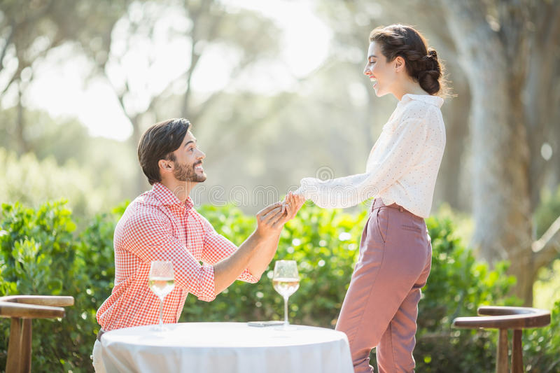 Man proposing a woman with a ring on his knee. In the restaurant royalty free stock photo
