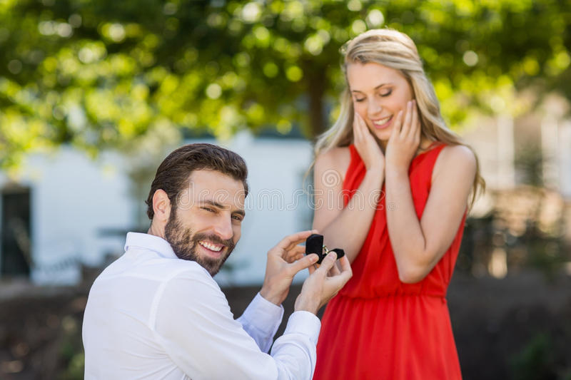 Man proposing a woman with a ring on his knee. In the restaurant royalty free stock photos