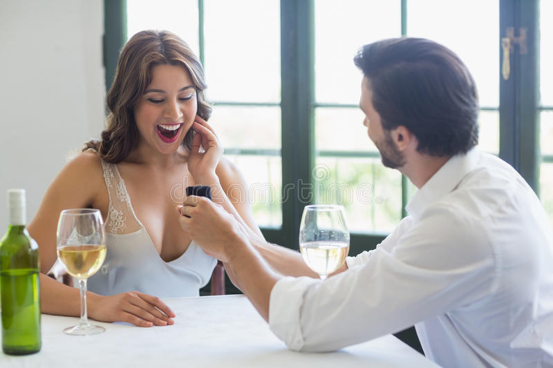 Man proposing a woman with a ring. In the restaurant royalty free stock images