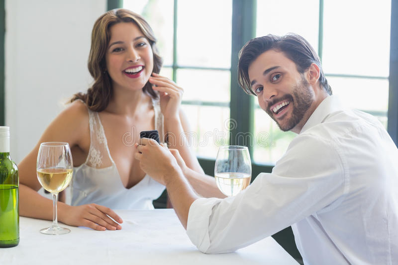 Man proposing a woman with a ring in the restaurant. Portrait of man proposing a woman with a ring in the restaurant stock photo