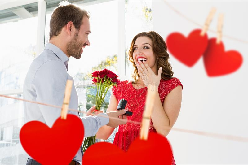 Man proposing woman on valentine day. With red hearts hanging in foreground stock image