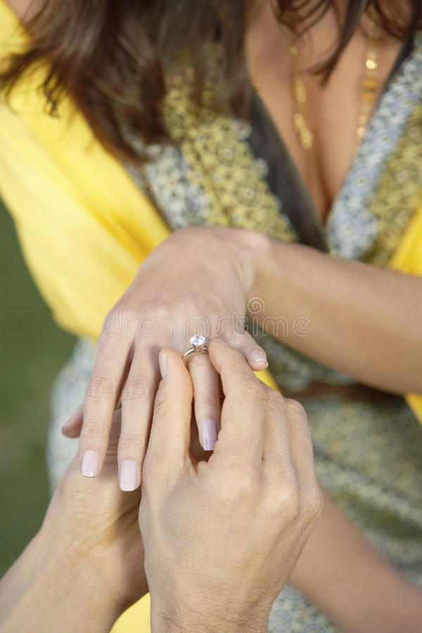 Man Proposing Women. Close up of a men placing a diamond engagement ring to a women's finger stock image