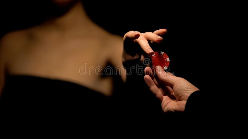 Man proposing woman poker chip, inviting for game, isolated on black background stock photo