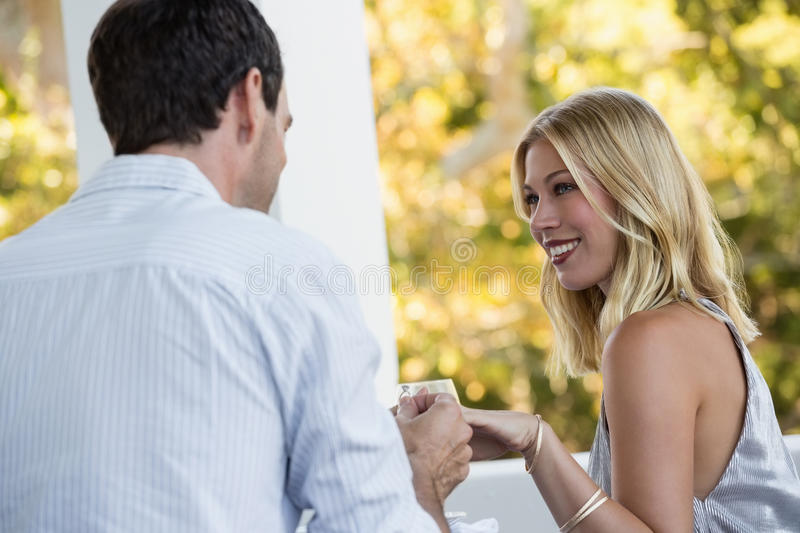 Man proposing young woman at restaurant. Rear view of men proposing young women at restaurant royalty free stock photography
