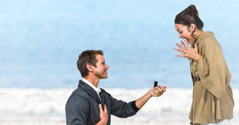 Man propsing to woman against blurry beach royalty free stock photo