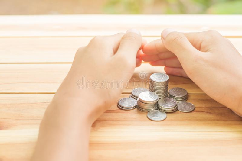 Man protecting house model on table, planning savings money of coins to buy a home royalty free stock photo