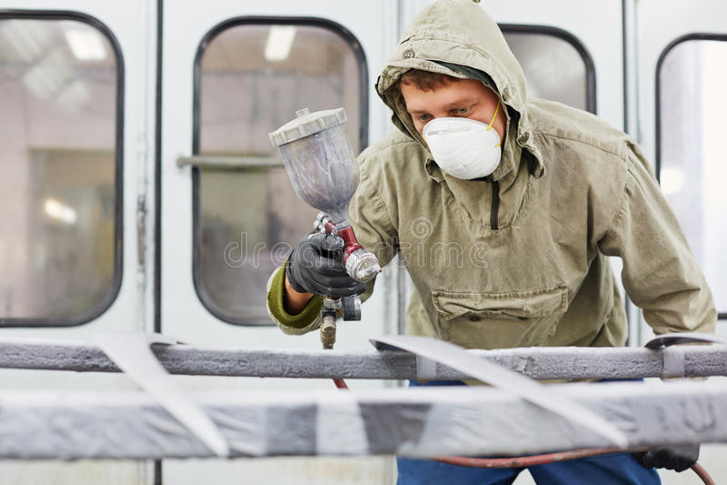 Man in protective clothes works in paint-spraying booth royalty free stock photography