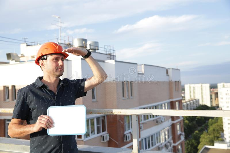 man in a protective helmet holds his hand at his head and looks into the distance while standing on the roof of a building. stock photography