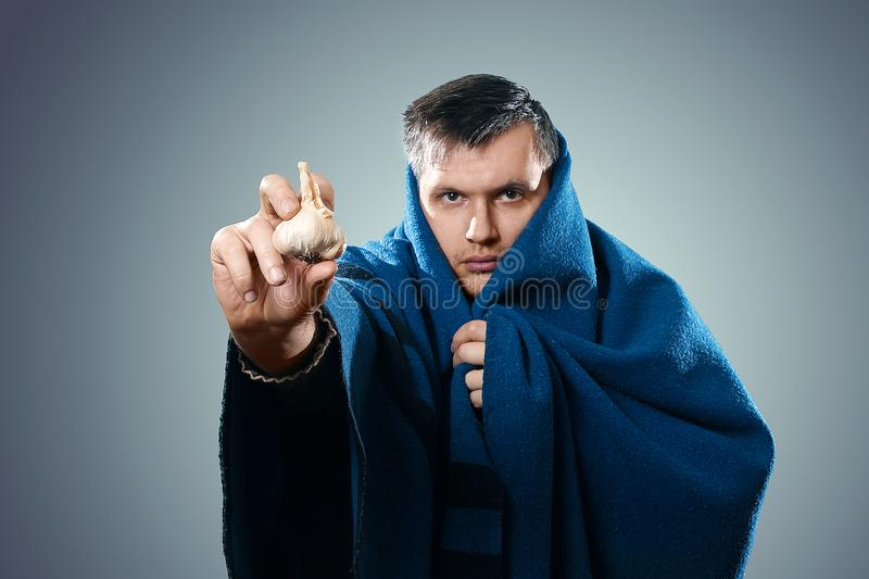 Man in protective mask against infectious diseases and flu. Photo of sick man holding a garlic. Close up. Healthcare concept stock photos