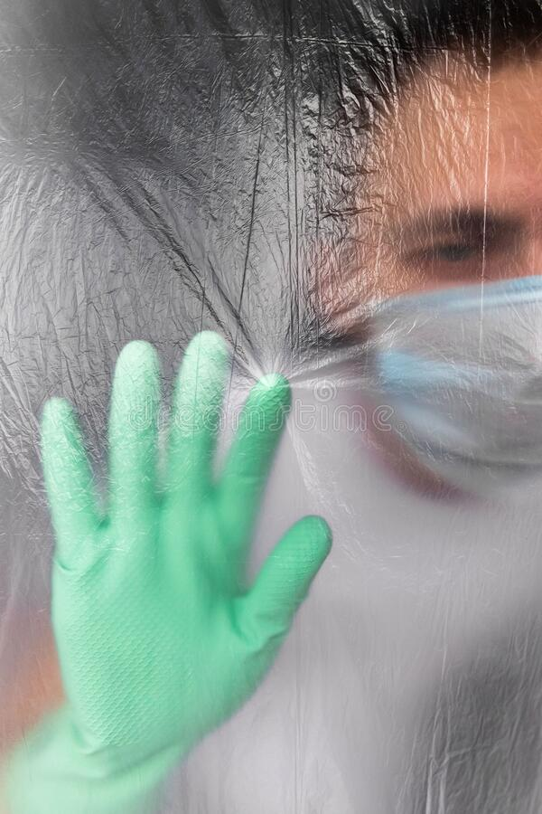 Man in protective mask and gloves self- in his apartment during coronavirus infection. So as not to infect his family, touching isolation membrane. Quarantine stock photo