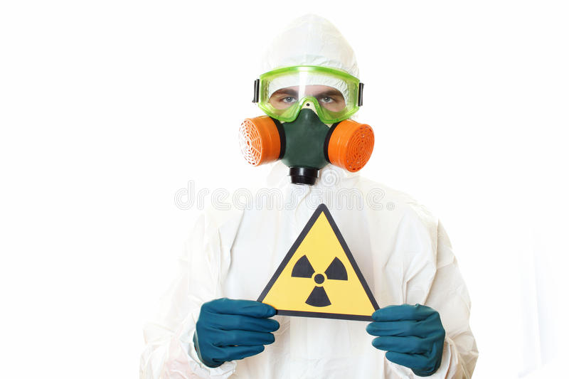 Man in protective suit. A mask and a respirator. Holding a sign warning of radiation. Isolated on white royalty free stock photo
