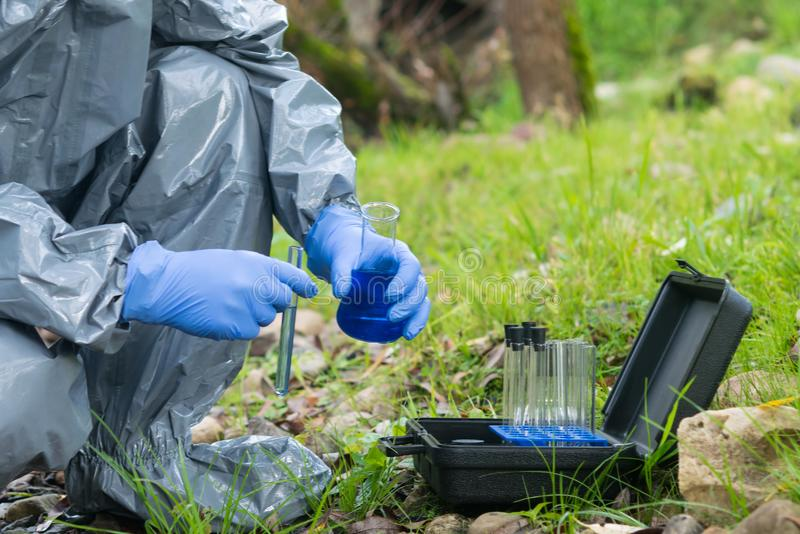 A man in a protective suit analyzes water in a mobile laboratory using special reagents. A man in a protective suit analyzes  water in a mobile laboratory using stock images