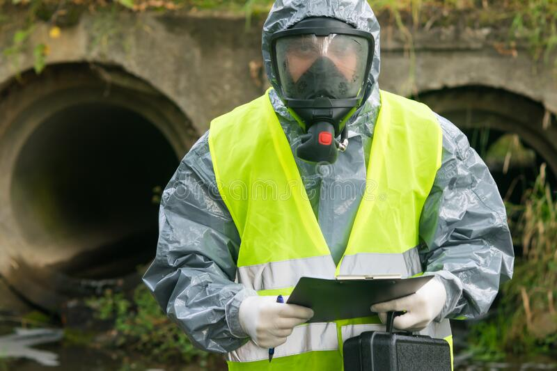 A man in a protective suit and mask holds a suitcase with equipment and a tablet in his hands to record research results stock image