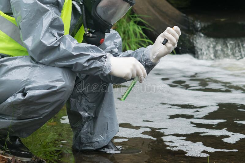 A man in a protective suit and mask holds a test tube and a pipette with test water on the river after an accident stock photography