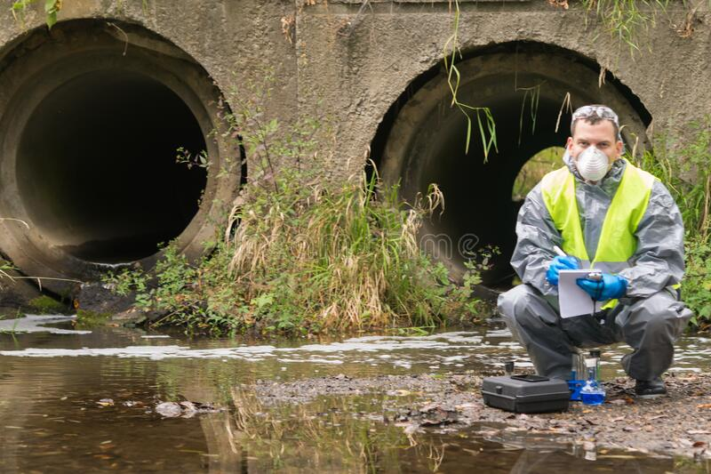 A man in a protective suit and mask keeps records in a report on the situation at the scene of an environmental accident royalty free stock photography