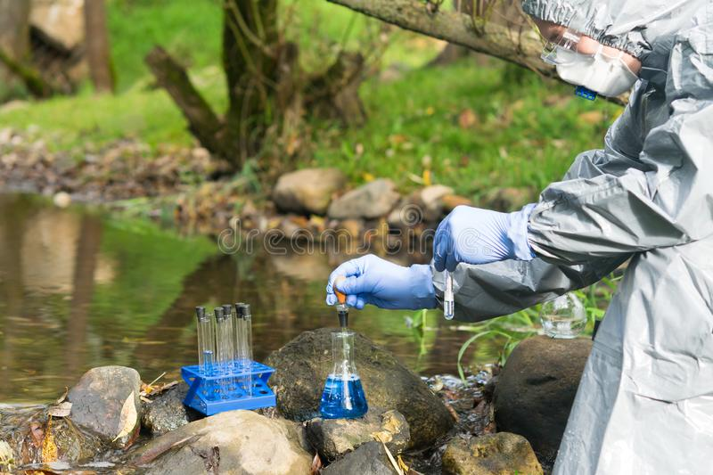 A man in a protective suit and respirator analyzes the water from the river in a portable laboratory using special reagents stock photography