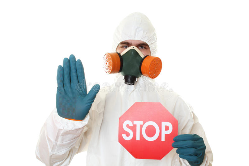Man in protective suit with a sign STOP. Man in protective suit and respirator holding a STOP sign. Isolated on white stock photography
