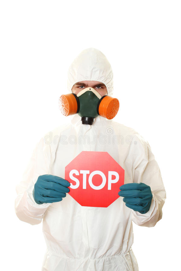 Man in protective suit with a sign STOP. Man in protective suit and respirator holding a STOP sign. Isolated on white royalty free stock images