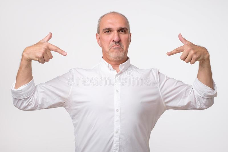 Man proud of himself over gray background. I am the best concept. stock photo