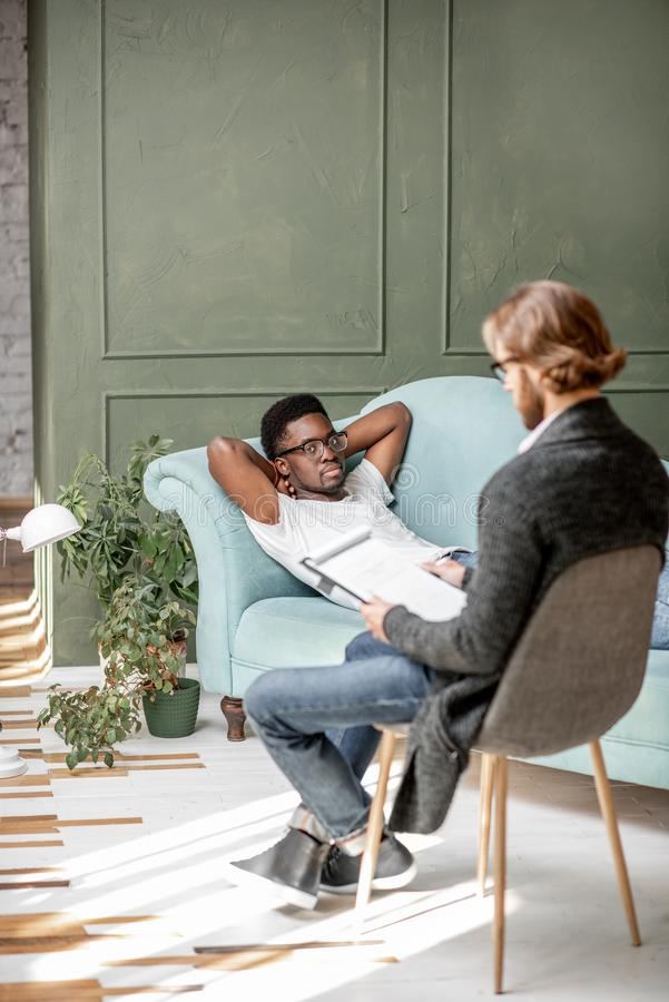 Man during a psychological session with psychologist. Young afro ethnicity men having a serious conversation with psychologist lying on the comfortable couch royalty free stock photos