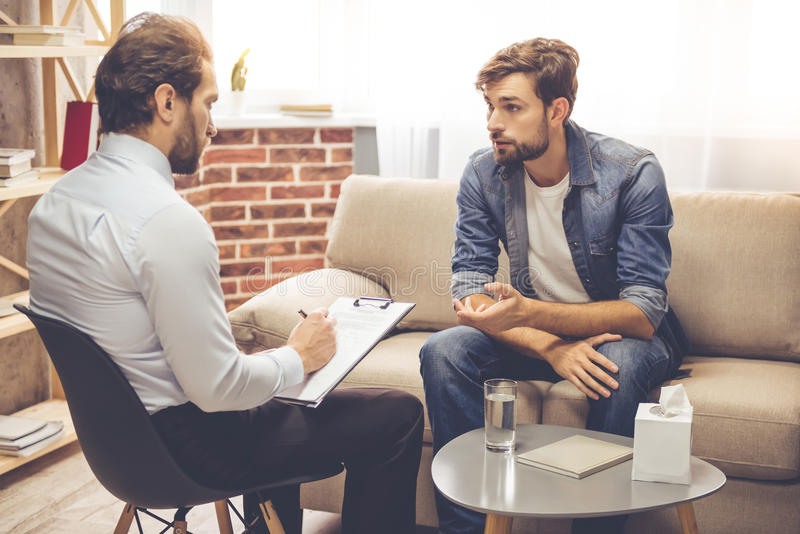 Man at the psychologist. Handsome young men is sitting on couch and talking to the psychologist while doctor is making notes royalty free stock photography