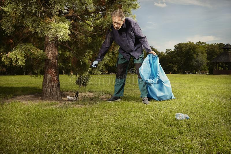 Man at work pick up garbage on grass in park stock photos