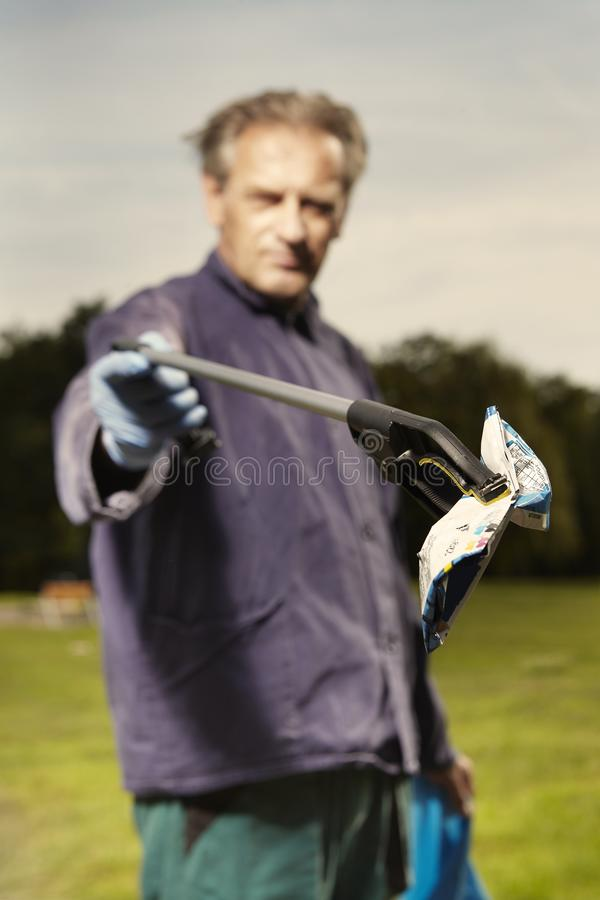 Man at work pick up garbage on grass in park royalty free stock image