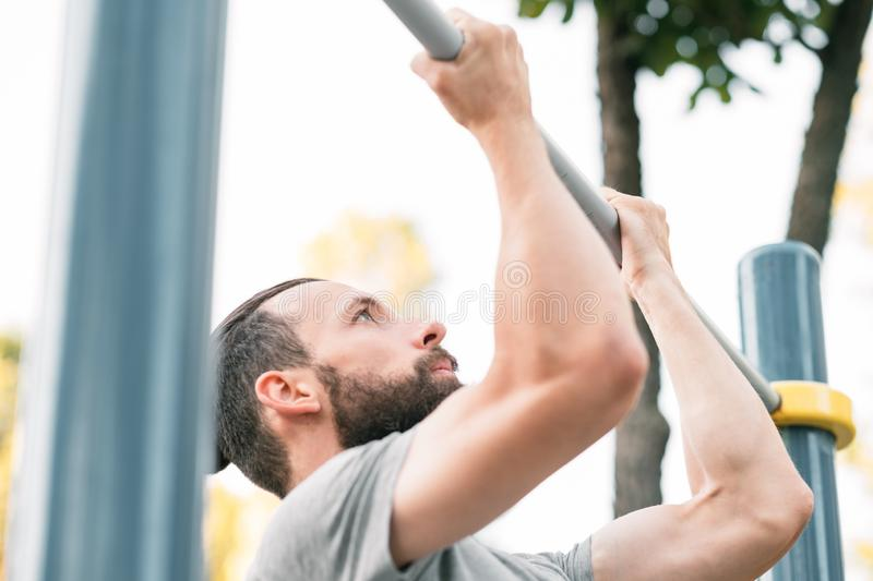 Man pull ups fitness wellness exercise training. Man doing pull ups. fitness and wellness exercises. physical training royalty free stock photos