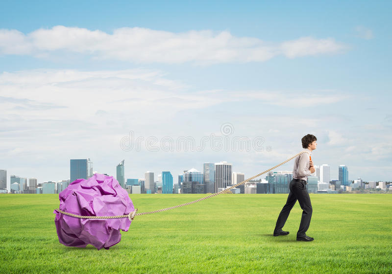 Man pulling with effort big crumpled ball of paper as creativity sign. Young businessman outdoors making huge paper ball move royalty free stock images