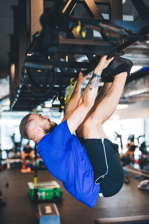 Man pulling his body up on the rig at the gym. stock photo