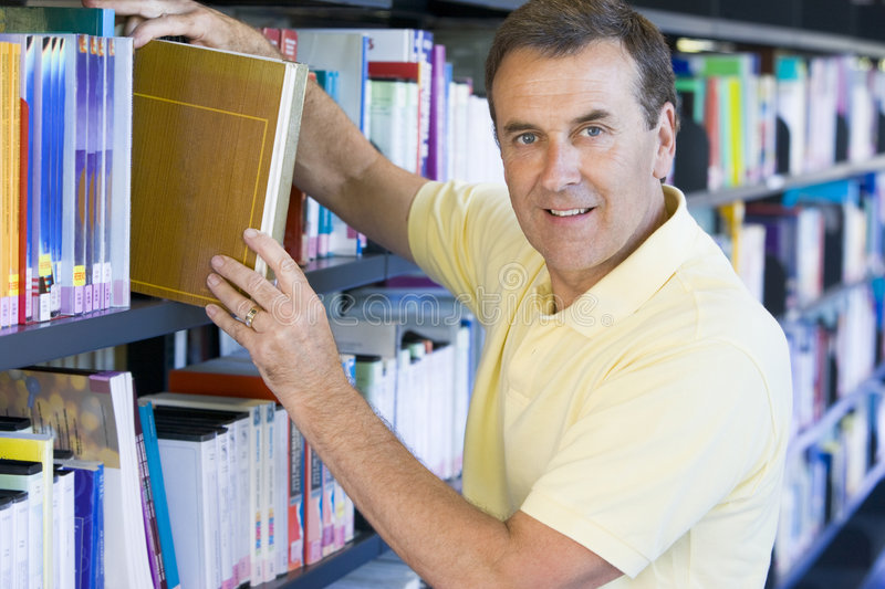 Man pulling a library book off shelf.  royalty free stock photo