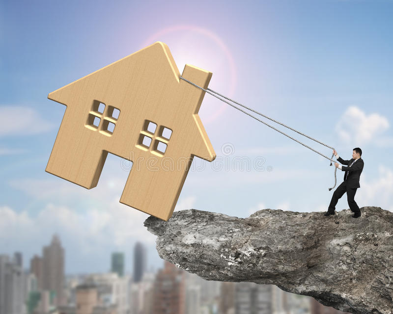 Man pulling rope to move wooden house on cliff edge. With sun sky cityscape background royalty free stock image