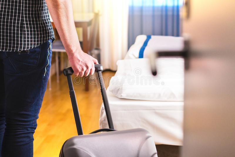 Man pulling suitcase and entering hotel room. Traveler going in to room or walking inside motel with luggage. Travel and holiday apartment rental concept stock image