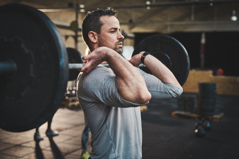 Man pulling up large barbell in fitness class royalty free stock photos