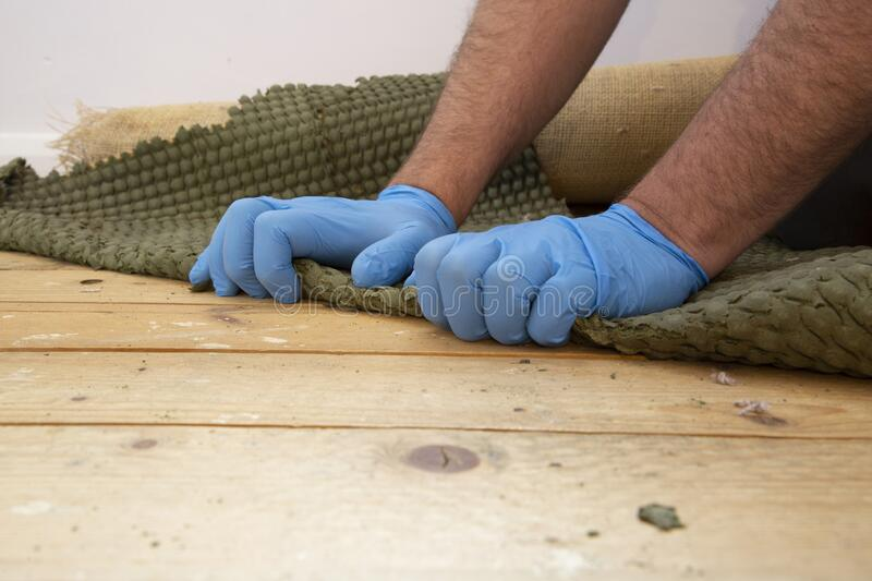 Man pulling up and removing carpet underlay from a wooden floor. royalty free stock photography