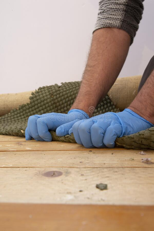 Man pulling up and removing carpet underlay from a wooden floor. stock image