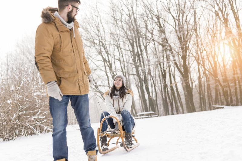 Man pulling woman on a sleigh. Beautiful young couple in love enjoying a winter vacation and having fun on a snowy winter day. Boyfriend pulling his girlfriend stock image