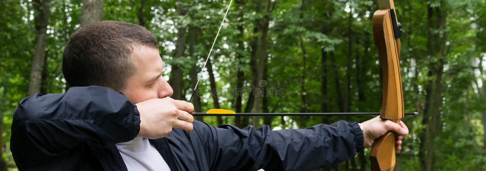 Man pulls a bow string for a shot in the forest, close-up, long photo stock photo