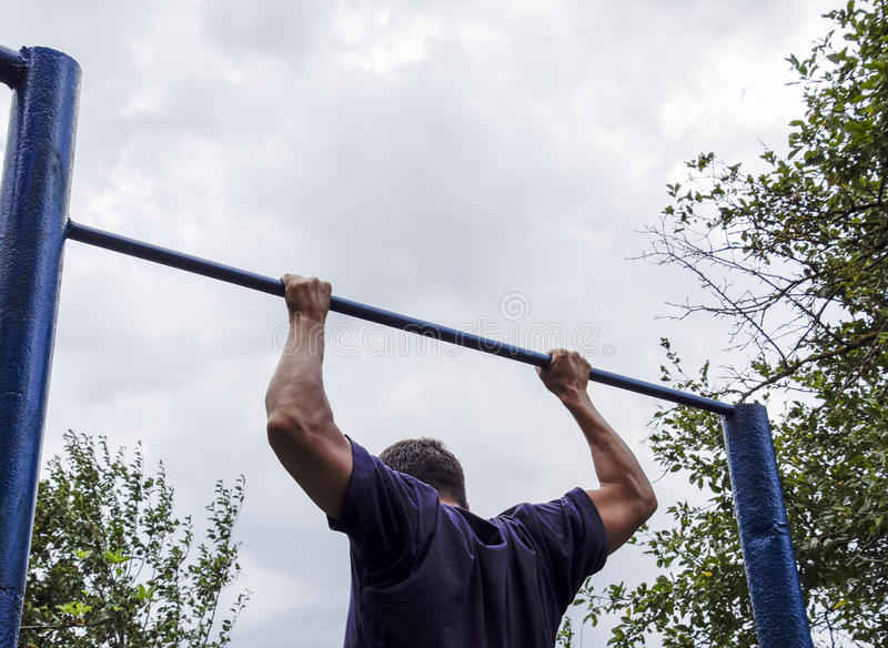 The man pulls himself up on the bar. Playing sports in the fresh air. Horizontal bar. The man pulls himself up on the bar. Playing sports in the fresh air stock photo