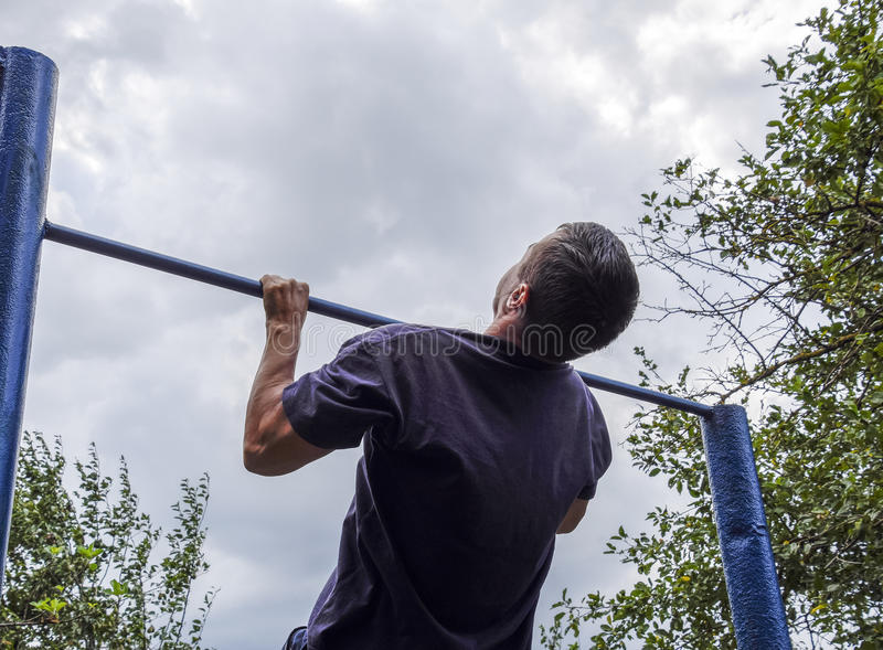 The man pulls himself up on the bar. Playing sports in the fresh air. Horizontal bar. The man pulls himself up on the bar. Playing sports in the fresh air stock photography
