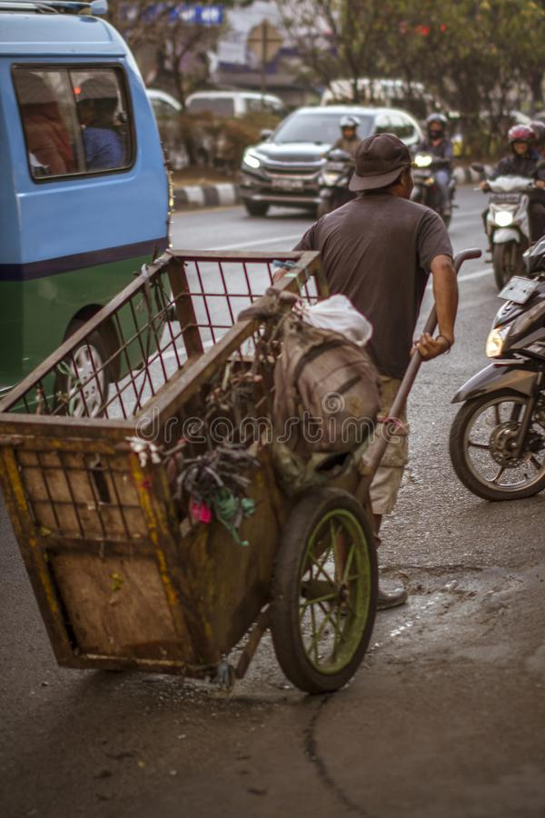 A man pulls rubbish collector cart on the street.  stock images