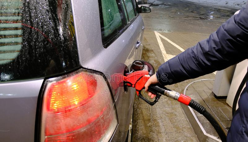 Man pumping gasoline into the car at the gas station-transportation concept. Man pumping gasoline fuel in car at gas station-transportation and ownership concept royalty free stock image