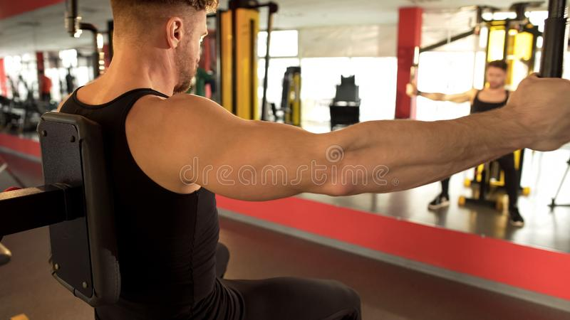 Man pumping his pectoral muscles in gym, looking at his reflection in mirror. Stock photo royalty free stock photography