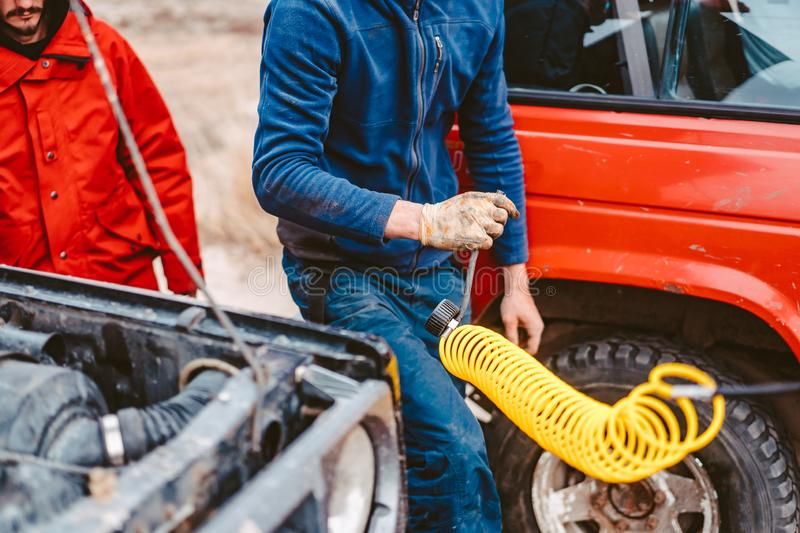 A man pumps air wheel with a compressor royalty free stock image