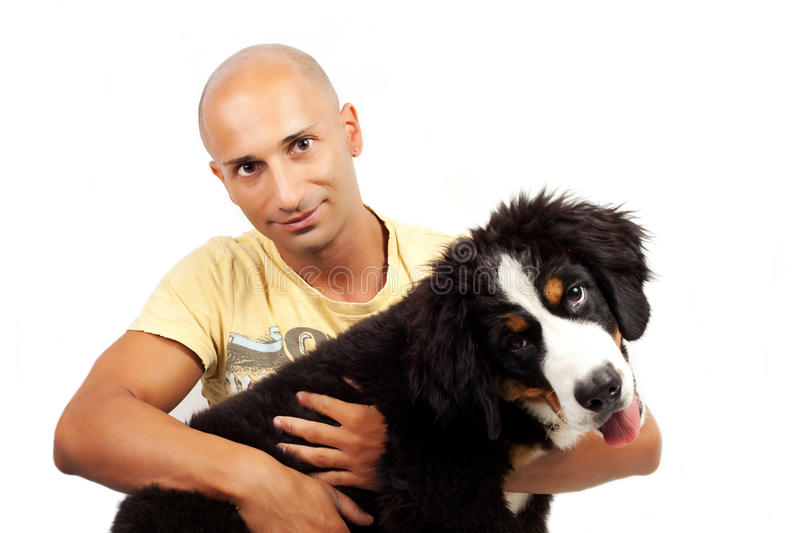 Man with puppy bernese mountain dog. On the white background royalty free stock image