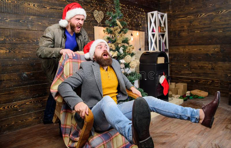 Man push armchair with friend. Cheerful men having fun at home. Christmas fun. You will never be bored if you have such. Friend. Break into new year with fun stock photography