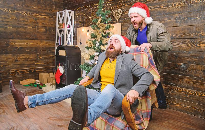 Man push armchair with friend. Cheerful men having fun at home. Christmas fun. You will never be bored if you have such. Friend. Break into new year with fun royalty free stock image
