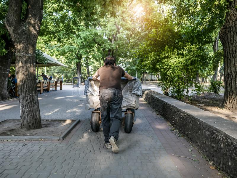A man pushes a cart in front of him stock photo