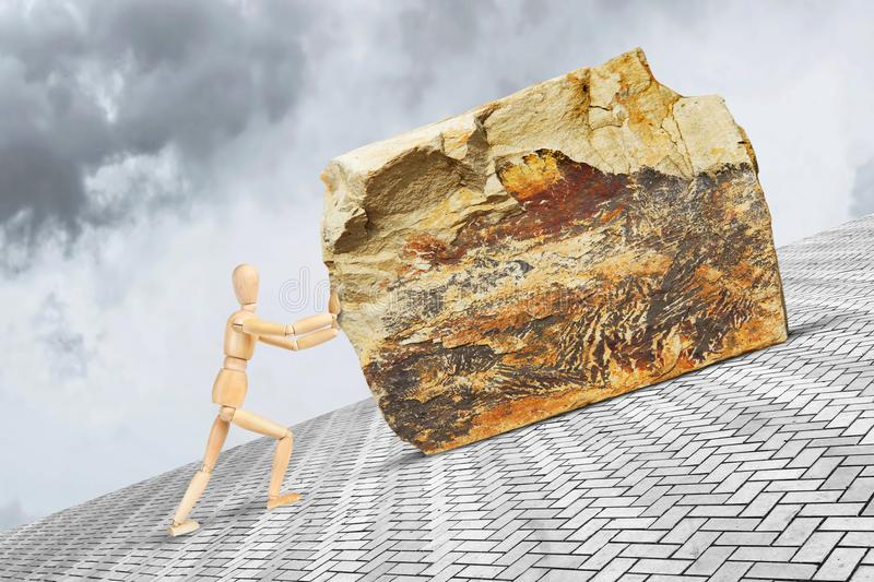 Man pushes the heavy and large stone upward along the slope with effort. Conceptual image with a wooden puppet royalty free stock image