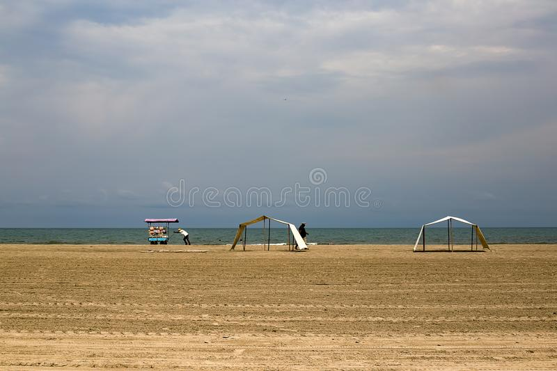 Man pushes his food cart on a desert beach royalty free stock images